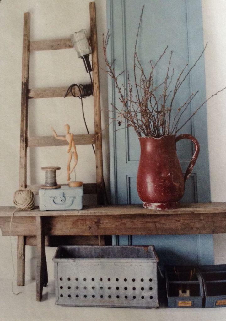 Sfeerhoekje met ladder en oude deur achter robuust houten bankje