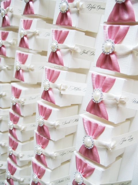 Personalised wedding favour boxes with rose pink satin ribbon, pearl brooch embellishment and wedding guest name tag from Amor Designs