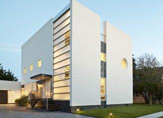 Delikatnie podświetlony budynek w jasnych barwach wydaje się być lekkim dodatkiem na trawniku