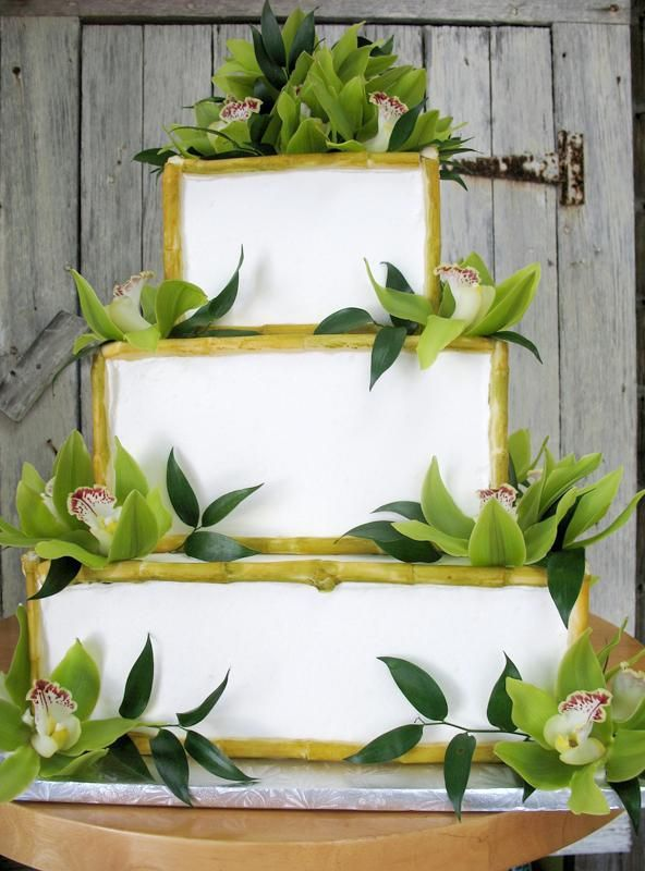 White wedding cake decorated with bamboo and orchids