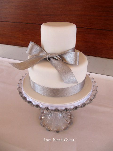 small cake covered in fondant and decorated with a silver bow