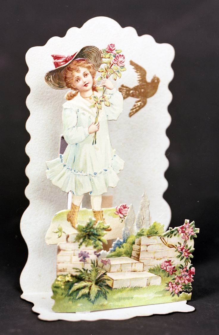 Pop-up valentine. Chromolithograph of girl in blue, holding a rose, standing by a garden wall. Gilt embossed scrap bird. Greeting on scrap on bottom: 'Loving greeting'. c.1890-1900 (OB1995.393)