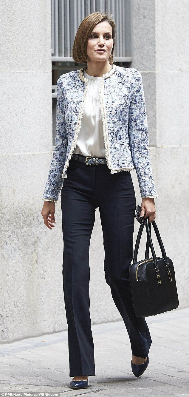 Dressed in on-trend high-waisted trousers teamed with a chic cream blouse and blue print j...
