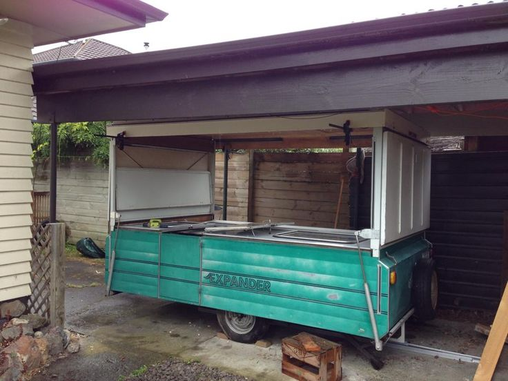The caravan partially unfolded. The ends fold out one at a time as the roof comes up. The clamps are from the renovation work.