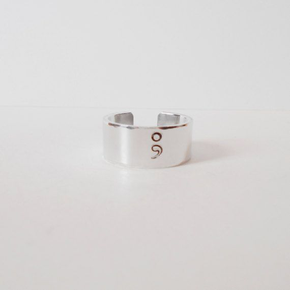 A hand stamped aluminium cuff ring with the semi colon symbol and the chance to have a message hand stamped on the inside.  A semi colon in outline has been hand stamped on the outside and I have gently hammered the edge of the ring to add detail. You can choose to have the inside plain or your own personal message stamped on the inside.  The cuffs are made from 1100/1050 Pure Aluminium which has a lower rate of skin reaction than other metals including sterling silver. It looks like sil...