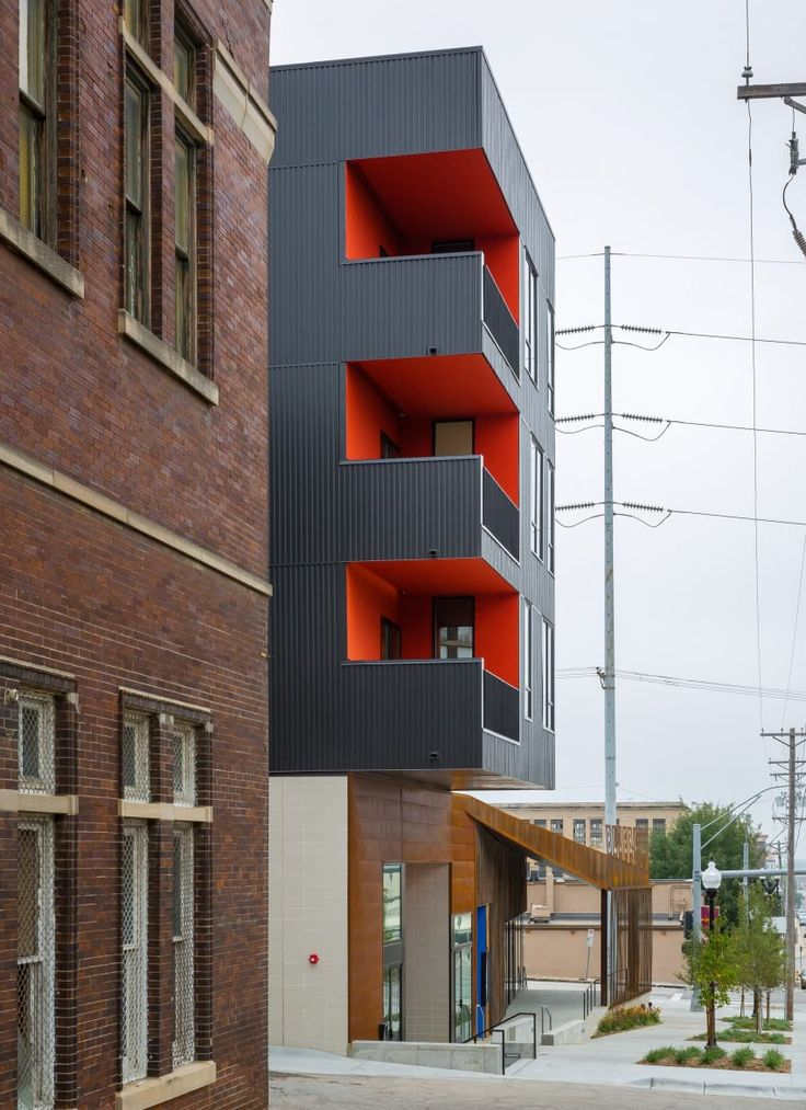 In contrast to its low-lying theatre, this building consists of a three-storey box clad in dark metal that slightly cantilevers over the ground level, which is faced with weathering steel. The ground level accommodates a restaurant, while the upper floors each contain a loft-style apartment.