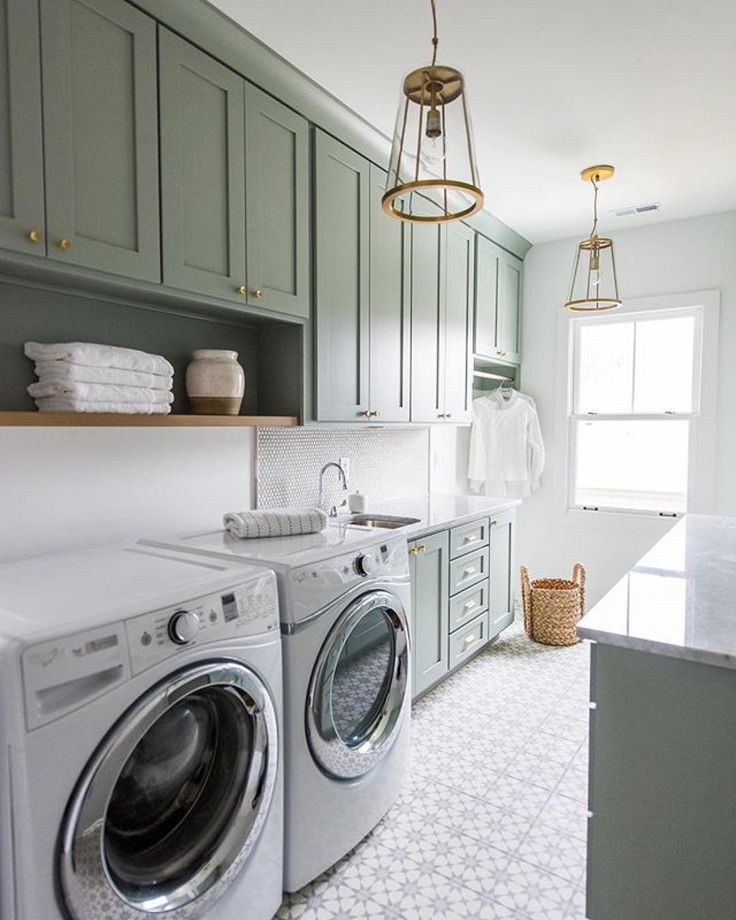 Well appointed gray green laundry room is