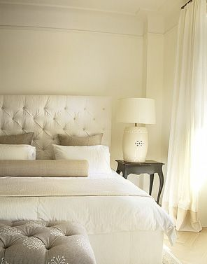 Pretty light filled bedroom. Tone on tone cream, white and gray colors throughout. Tufted cream headboard against creamy white wall. Chinese garden stool lamp in cream. Contrasting black nightstand.