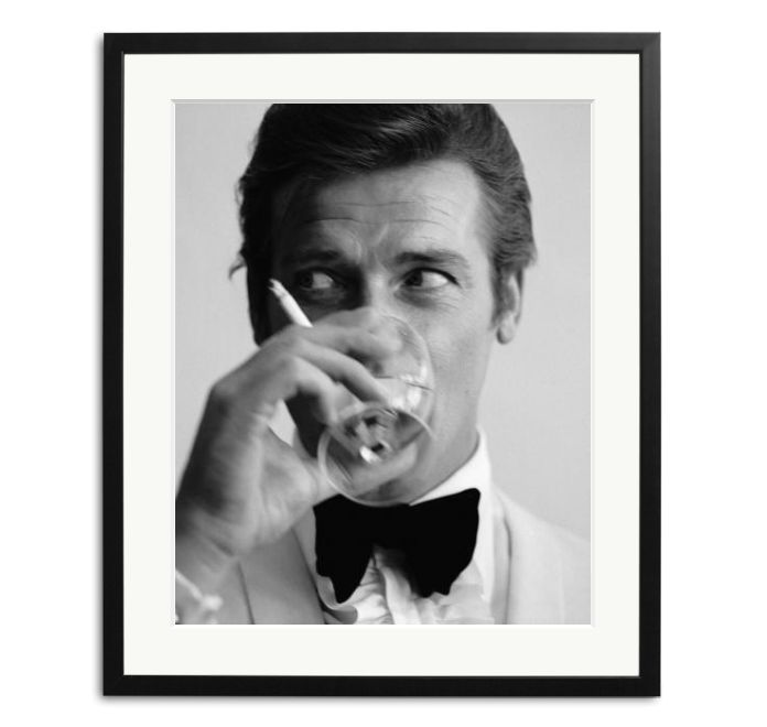 English film star Roger Moore, well known for his roles as James Bond and the Saint, downs a martini.