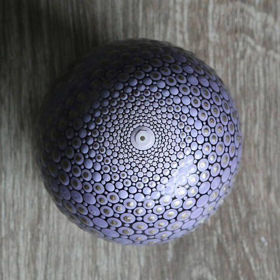 Mandala bal beschilderd met lila, bruine, grijze en metaalkleurige acrylverf. De diameter van de bal is ongeveer 8 cm. De bal is gemaakt van helder glas en afgewerkt met glanzende vernis. Maar kan alsnog niet gebruikt worden voor buiten, etc. Op de vierde foto is als voorbeeld te zien hoe de mandala bal verpakt is in een organza zakje met een metalen ringetje (waar de bal opgeplaatst kan worden). Leuk om dus kado te geven! Bijvoorbeeld voor een huwelijk, housewarming, geboorte of yoga…