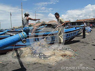 Yogyakarta, Indonesia. February 20th, 2010. Indonesian fishermen clean the fishing net at Parangtritis Beach.