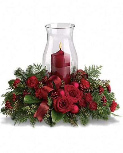 Holiday Glow Centerpiece   T115-3A      It's beginning to look a lot like Christmas! Add a warm glow to your holiday décor with this lush arrangement of red roses and carnations. A beautiful Christmas centerpiece with its classic glass hurricane and red pillar candle, it also looks lovely on a mantle or entry table.        https://www.4165flower.com/index.asp?pid=4=viewproduct=10341=1