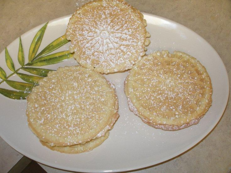 Pizzelle:  Need a Pizzelle Press Mixer 4 cups all purpose flour 12 eggs 2 cups of sugar 1 1/4 cup canola Oil Vanilla extract (to taste) Anisette (to taste) powdered sugar - cookingwithnonna.com
