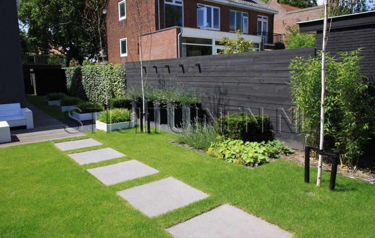 TUIN. Pad van grote grijze tegels door het gras, grote bloembakken naast elkaar met vaste planten/ lavendel, terras met banken op vlonders. Het geheel oogt rustig. Schutting ook mooie kleur