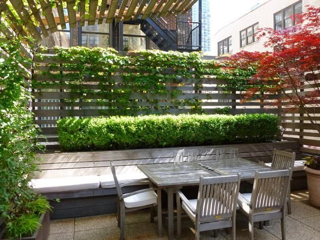 LOVE how the fence curves over the patio. Would be great for pool! green fence and wall design for outdor home decorating with flowers and plants