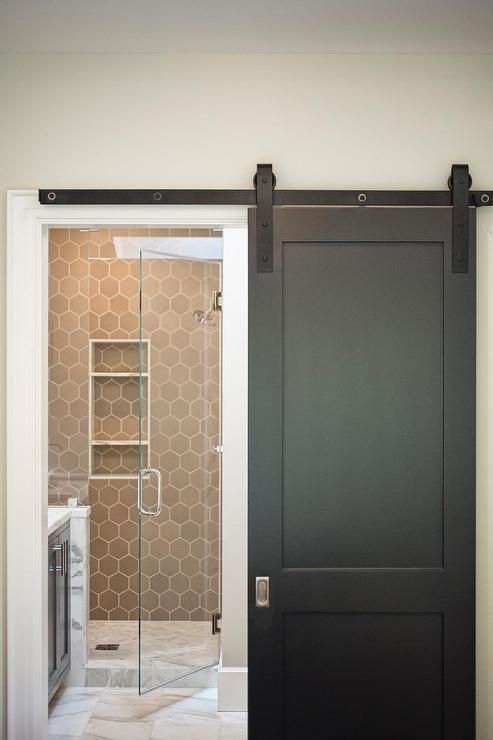 a black sliding door on rails opens to a en suite bathroom boasting a walk