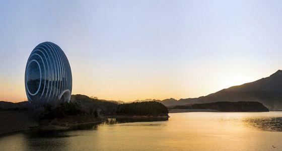 """Yanqi Lake Kempinski (Beijing, China). Parece mentira pero es verdad. Desde el pasado noviembre, una especie de caracol de cristal de casi 100 metros de altura aparece depositado junto al lago Yanqi, a una hora del centro de Beijing. Conocido como Sunrise Kempinski, este """"hotelito"""" representa el frenético desarrollo del poderío chino, su sol naciente. De lado, parece la concha de una vieira, símbolo de fortuna y prosperidad. Pues vale."""