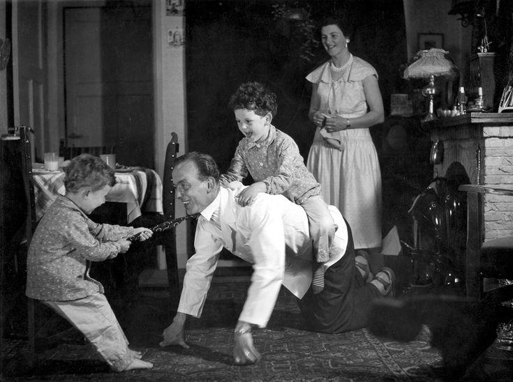 Huiselijk tafereel: Nederlands gezin in de jaren '50. Vader speelt voor de kolenkachel met de kinderen (paardje rijden), terwijl moeder lachend toekijkt, [1956].