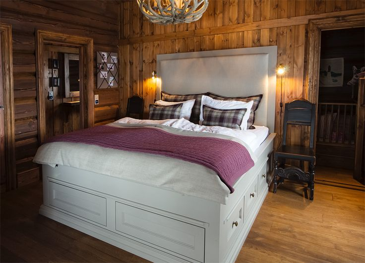 Cozy bedroom in mountain cabin. Bed from Os Trekultur, with drawers under the bed that provides good storage. Handpainted in light grey, goes well with the timberwalls.