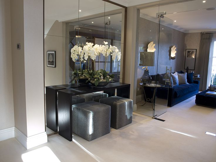 Orchids in a black bowl | fabulous mirrored wall and contemporary console table with cube seating