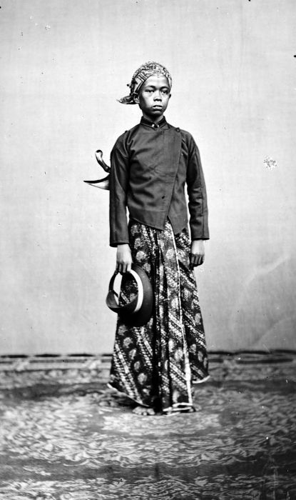 A teenager in Java wearing traditional Javanese attire: blangkon headgear, batik sarong and kris as accessory. 1913.
