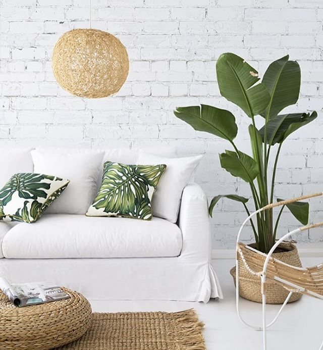 Who isn't obsessed with indoor plants and palm frond print right now? This living room is perfection from the wicker to the plants to the white brick wall