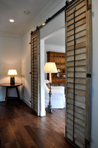 White plantation shutters on barn door sliders for a sliding glass door cover!
