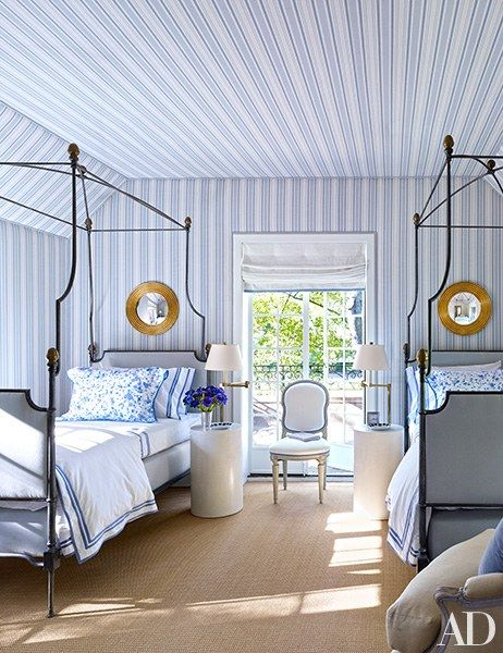 A guest room lined with blue and white striped wallpaper and brass canopy twin beds | archdigest.com