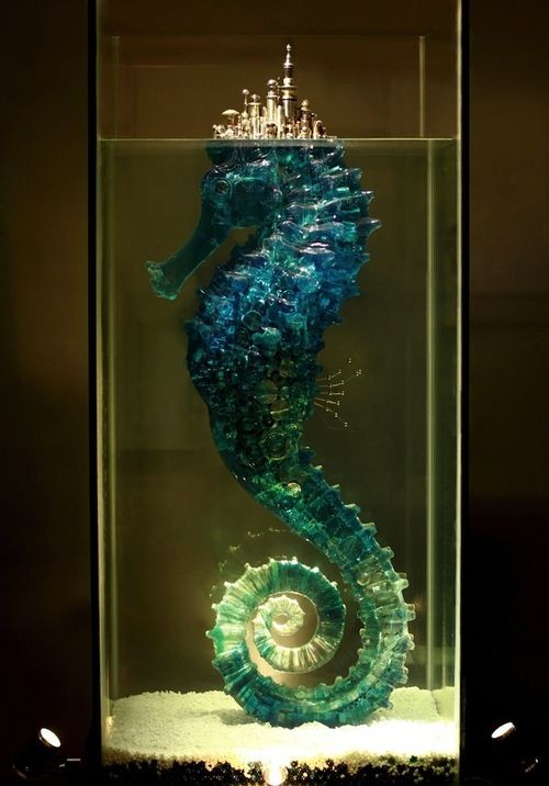 "From io9: Chinese sculptor Hu Shaoming. Hu explains that the seahorse piece, titled ""City of Dreams,"" is actually about the broken nature of its fairy tale premise, the idea that nature is supporting humanity's urban dreams, and will one day be exhausted. The golden series, his ""Umbrella"" series, contains by his count 2,000 individual buildings, made of metal from buttons, clothing accessories, utensils, food containers, furniture fixtures, and other odds and ends of daily life."
