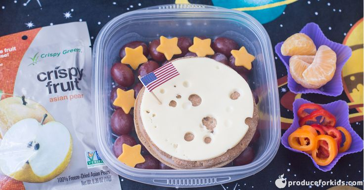 """Blast off! This bento box is definitely out of this world! Whether your kids have a love of space or are just learning about it in school, it'll be all smiles when they open this lunch. Grapes create the dark backdrop while Swiss cheese is the perfect place for a moon landing. Don't forget about the clementine crescent moons and mini sweet pepper """"planet rings"""" to round out the meal."""
