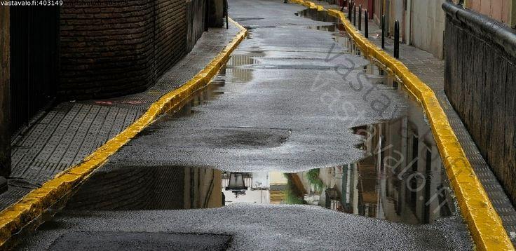 Kuva: Sateen jälkeen - lätäkkö lammikko viiva maalaus tiemerkintä katu heijastus keltainen - Kuvatoimisto - Photostock Vastavalo.fi
