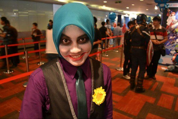 The Joker Playing on the Joker's signature green and purple color palette, don a green hijab with a purple shirt, a tie, and creepy face makeup.
