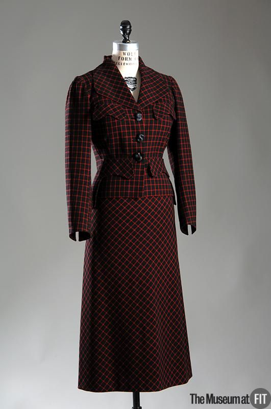 "Suit, Elsa Schiaparelli (1890-1973): ca. 1935, French, wool. ""Elsa Schiaparelli may have been best known for her whimsical approach to fashion, but her designs for tailored, functional suits were also quite successful. This example's red-checked wool hints at the bold colors that characterized Schiaparelli's palette, and the large, plastic ""S"" buttons emphasize her love for playful details..."""