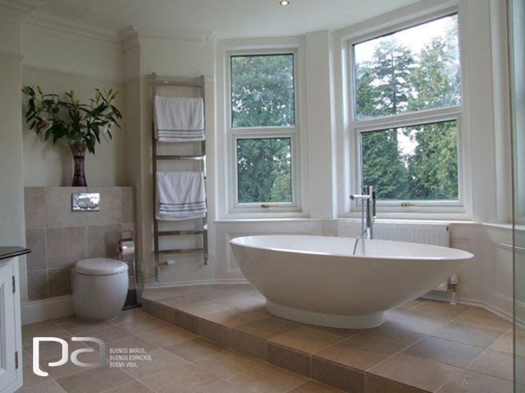 La tina Napoli de Victoria + Albert logra ser el centro de atención de este bello baño neutral en Devon, Reino Unido. El suelo, de color beige claro, y los azulejos de las paredes utilizados, en conjunto con la madera blanca, forman un espacio que invita a la relajación y a disfrutar de un baño.  Victoria Albert exclusivo en Productos Arquitectónicos