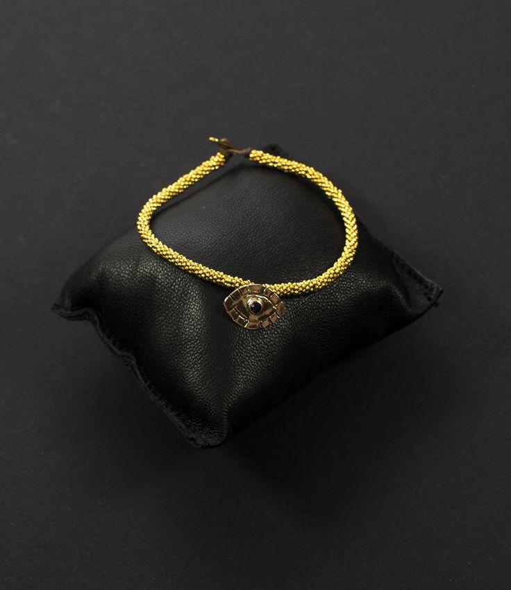 """Gorgeous 24 carat gold India bracelet with evil eye, on a ultra strong and soft waxed string. Indulge yourself with these unique and handmade pieces byJeweler to the Stars Studio Paras.Prefer silver? Find those here.  Material & dimensions    24 carat gold   evil eye   small = """"17 cm   medium = """"18 cm  Jewels for jaded rock stars,self- righteous DJs and you!"""