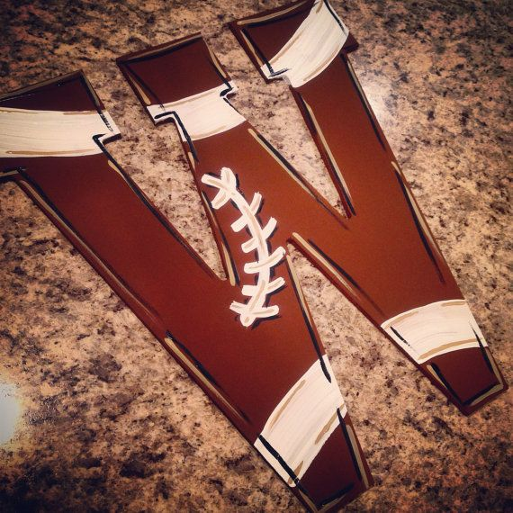 This listing is for one single hand-painted 13 wooden football themed door hanger. Great for nursery letters or for your front door!  In the Notes To Seller area at checkout, please specify the letter(s) you would like, along with any customizations.  The item shown is only an example and is not the exact item you will receive. Can be customized. Attached to wire for hanging. Painted with acrylic paint and sealed with a coat of polyurethane.  In order to get the most life out of this…