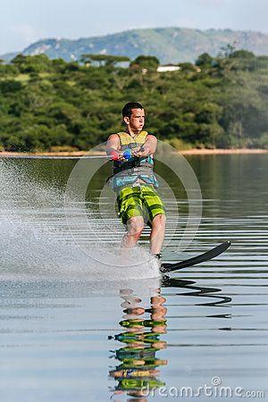 Mature male water-skiing slalom single ski on glass mirror waters