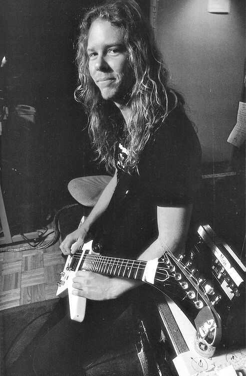 James Hetfield holding his guitar while practicing in the studio.