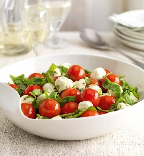 An Italian inspired salad of tomatoes and balls of mozzarella with spinach leaves, tossed in a basil oil dressing.