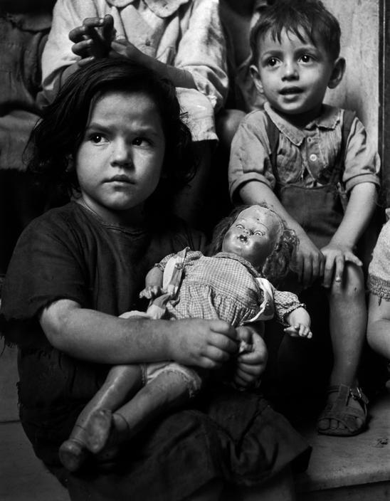 Napoli: Una bambina con la sua bambola malconcia, in attesa per la distribuzione del latte ad un ONMI (Organizzazione Nazionale per la protezione dei bambini e delle madri) Italia, 1948 da David Seymour