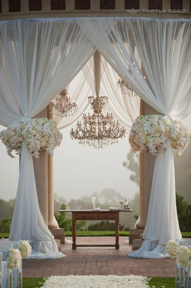 The outdoors, the drapery, the flowers, the chandelier... this wedding ceremony set-up is simply breath-taking!