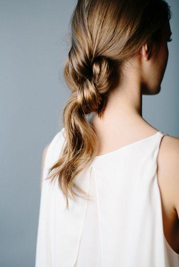 こちらは、2つに分けた毛束を2回結んだだけ。短い方の毛先を、結び目の内側にピンで固定します。