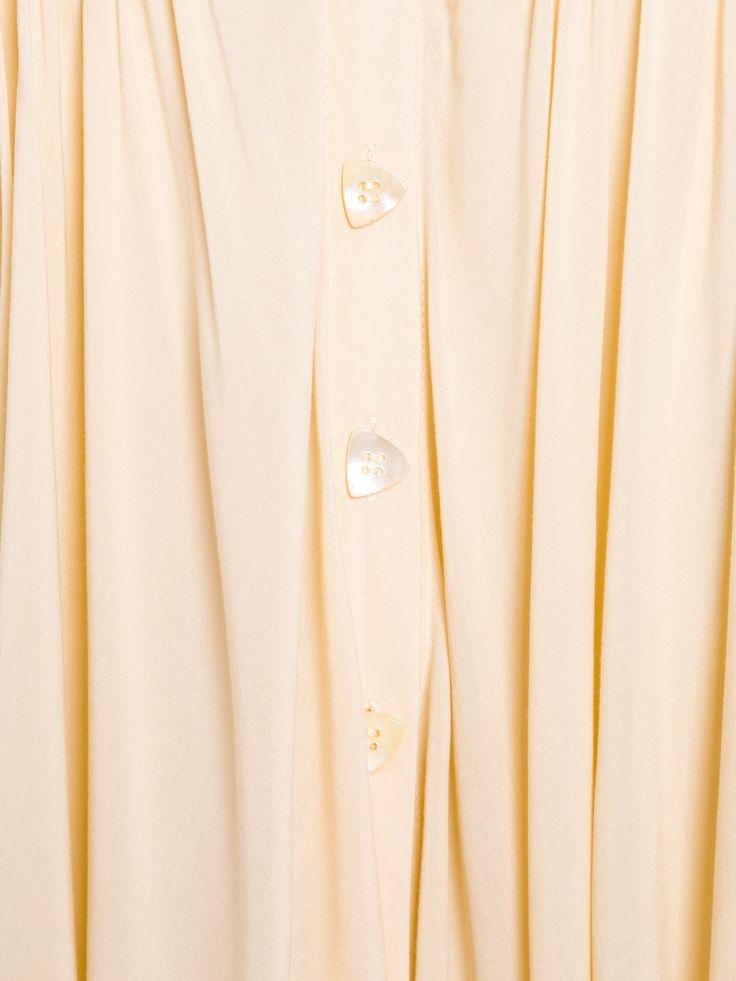 Calça Saia - Cris Barros - Creme  Calça Saia, Cris Barros.  A calça saia creme é confeccionada em tecido leve, possui caimento assimétrico, detalhe drapeado, cintura alta e abotoamento frontal.