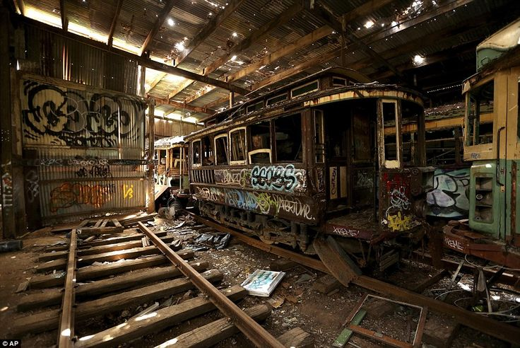 old tramcars and trolley buses sit abandoned and wrecked in the loftus tram shed in sydney, au