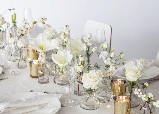 Dalebekken vaser fylt med roser, amaryllis og nelliker gir et vakkert nyttårsbord