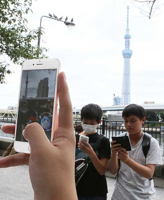 配信後初の週末を迎え、スマートフォン向けゲーム「ポケモンGO(ゴー)」で遊ぶ高校生=2016年7月23日午後、東京都台東区【時事…