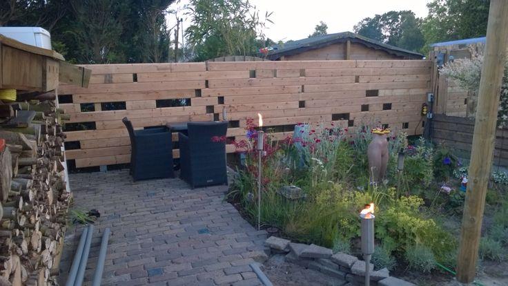 Speelse schutting van gebruikte blokhut planken.