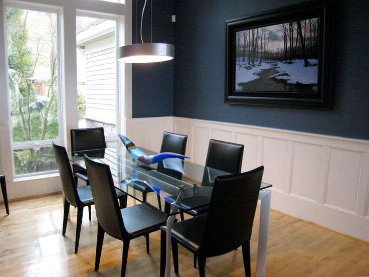 This Stylish Glass Table Is Trimmed With Sophisticated Black Chairs And A Navy Blue Accent Wall
