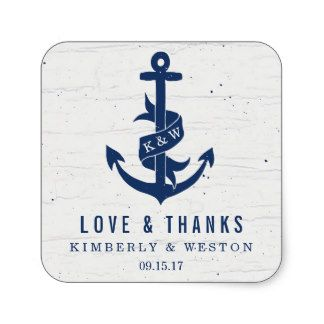 A navy blue anchor on a wood like off-white background.  The ribbon on the anchor displays the couple's initials (or any other custom text).  Perfect for a nautical themed wedding, especially when going with a rustic or vintage style.