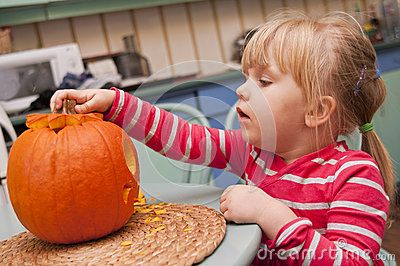 A cute young girl making her halloween pumkin at home.